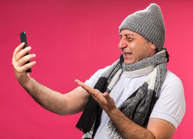 Genervter erwachsener kranker kaukasischer mann mit schal um hals, der wintermütze hält und auf telefon zeigt, das auf rosa wand mit kopienraum lokalisiert ist