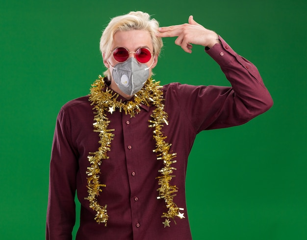 Genervter junger blonder mann, der brille und schutzmaske mit lametta-girlande um den hals trägt, der kamera betrachtet, die selbstmordgeste lokalisiert auf grünem hintergrund tut