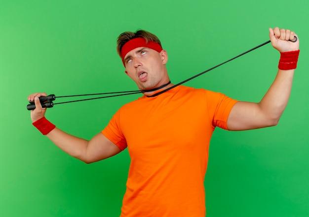 Genervter junger hübscher sportlicher mann, der stirnband und armbänder trägt, die selbstmord gestikulieren, der sich mit dem auf grün isolierten springseil erstickt