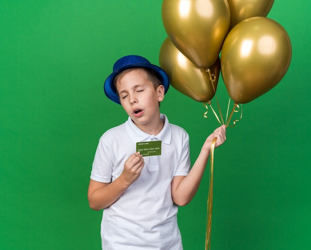 Genervter junger slawischer junge mit blauem partyhut, der heliumballons und kreditkarte lokalisiert auf grüner wand mit kopienraum hält