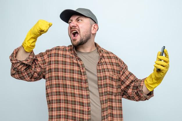 Genervter slawischer putzmann mit gummihandschuhen, der das telefon hält und die faust hebt