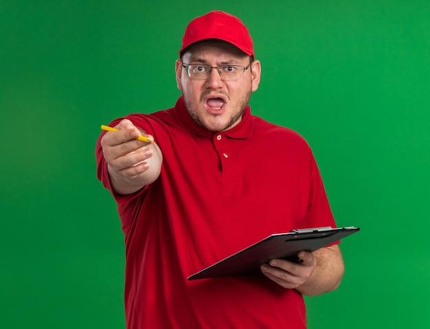 Genervter übergewichtiger junger lieferbote in der optischen brille, die klemmbrett und bleistift zeigt lokalisiert auf grüner wand mit kopienraum