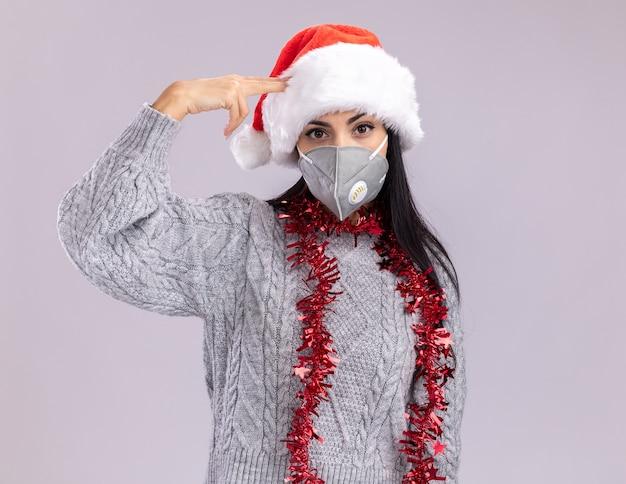 Genervtes junges kaukasisches mädchen, das weihnachtsmütze und lametta-girlande um den hals mit schutzmaske trägt, die selbstmordgeste tut, die auf weißer wand mit kopienraum lokalisiert wird