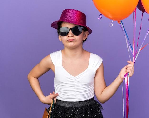 Genervtes junges kaukasisches mädchen in sonnenbrille mit violettem partyhut, der heliumballons und einkaufstaschen lokalisiert auf lila wand mit kopienraum hält