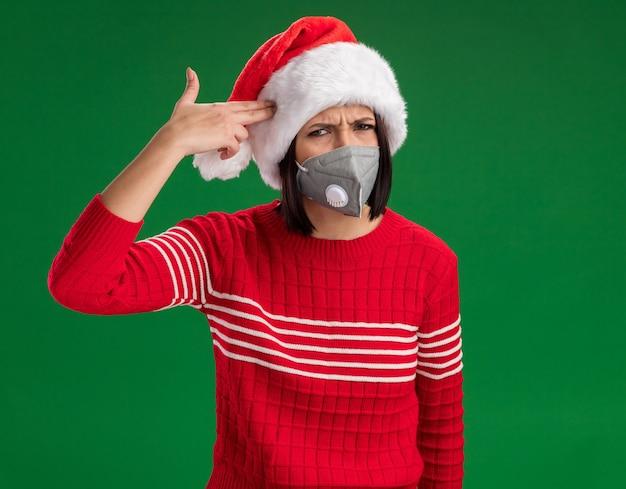 Genervtes junges mädchen, das weihnachtsmütze und schutzmaske trägt, die selbstmordgeste tut, die auf grüner wand lokalisiert wird