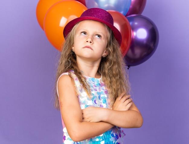 Genervtes kleines blondes mädchen mit violettem partyhut, das mit verschränkten armen vor heliumballons steht, die isoliert auf lila wand mit kopienraum suchen