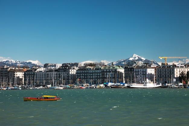 Genf panoramablick über gelbes schiff, gebäude und berge