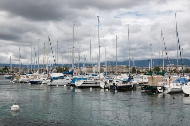 Genf, schweiz - 1. juli 2017: blick auf den genfer see mit booten und stadt genf, schweiz, europa. sommerlandschaft, sonnenscheinwetter, dramatischer bewölkter himmel
