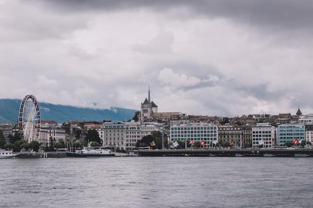 Genf, schweiz - 1. juli 2017: blick auf genfer see, weit entfernte berge und stadt genf, schweiz, europa. sommerlandschaft, sonnenscheinwetter, dramatischer bewölkter himmel
