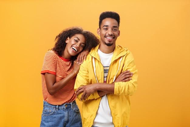 Genial, wenn der freund das beste freundporträt einer charmanten, freundlichen afroamerikanerin ist, die sich auf einen mann stützt, der seine schulter berührt, sich glücklich fühlt, dass sie zusammen sind und sie sich darauf verlassen kann, eine orangefarbene wand zu posieren