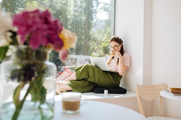 Genieß deinen kaffee. erfreutes mädchen, das auf der fensterbank sitzt und weltnachrichten liest