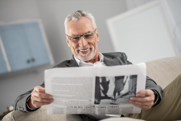 Geniesse dein leben. hübsche männliche person, die zu hause ist und lächeln auf seinem gesicht hält, während artikel liest