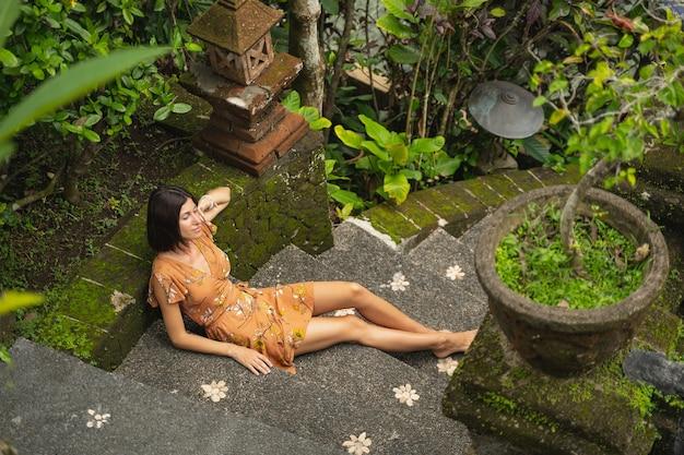 Genieße den moment. erfreute weibliche person, die auf der treppe sitzt, während sie allein über die natur meditiert