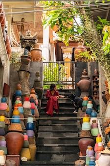 Genieße den moment. freundliches brünettes mädchen, das auf der treppe sitzt und sich während des spaziergangs ausruht