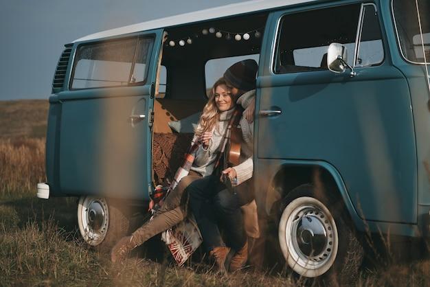 Genieße ihre gemeinsame zeit. hübscher junger mann, der gitarre hält und seine schöne freundin umarmt, während im blauen retro-art-minivan sitzt