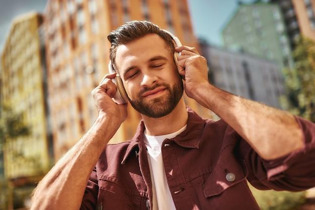 Genieße mein lieblingslied. hübscher junger bärtiger mann mit kopfhörern, der musik hört und die augen geschlossen hält, während er auf der straße steht. inspiration. musikkonzept. klang