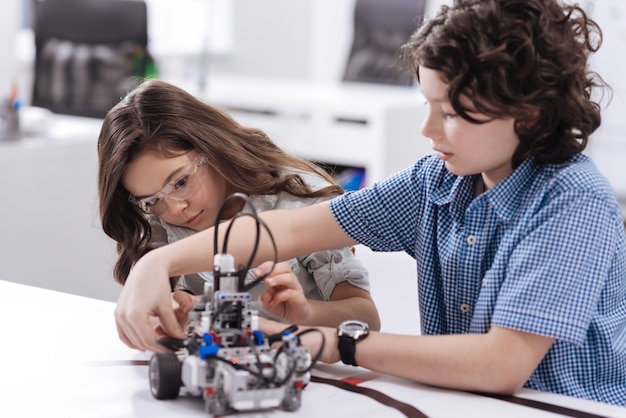 Genieße unser wissenschaftliches abenteuer. geschickte einfallsreiche geniale kinder, die in der schule sitzen und roboter schaffen, während sie freude ausdrücken