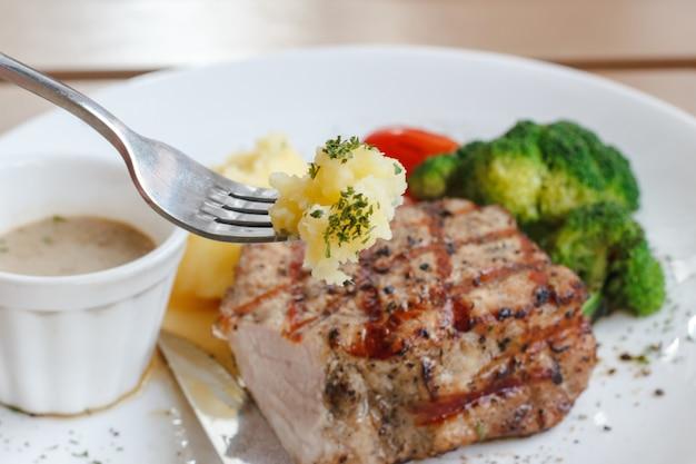 Genießen sie, biss der breikartoffel mit gabel und schweinefleisch saftigem steakhintergrund zu essen