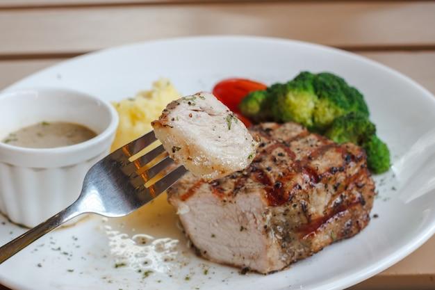 Genießen sie, biss von saftigem steak mit gabel zu essen und hintergrund zu verwischen