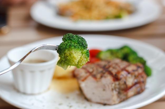 Genießen sie, bissen des brokkolis mit gabel und schweinefleisch saftigem steakhintergrund zu essen