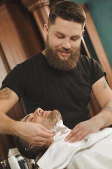 Genießen sie den modernen friseursalon. vertikales porträt eines mannes, der am lokalen friseursalon rasiert erhält