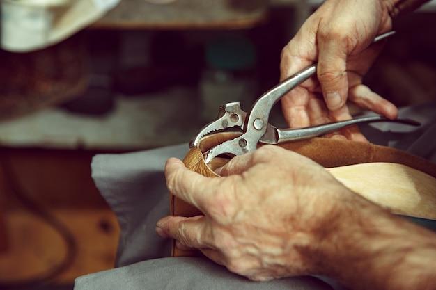 Genießen sie den prozess der herstellung von bastelschuhen. arbeitsplatz des schuhdesigners. hände des schuhmachers, der sich mit schusterwerkzeug befasst, nahaufnahme