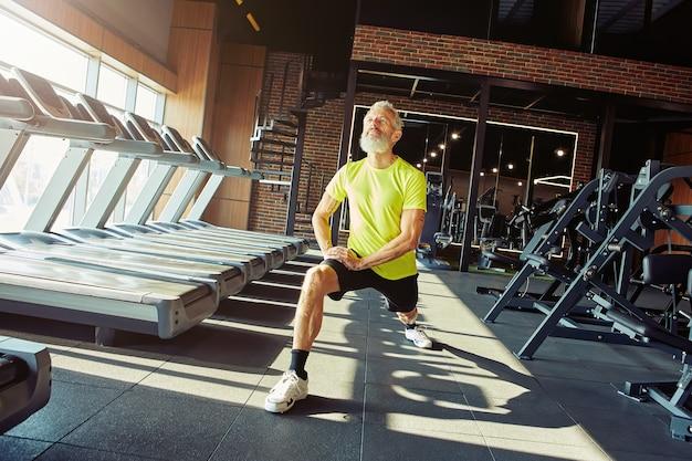 Genießen sie den sport in jedem alter in voller länge aufnahme eines athletischen, reifen mannes in sportbekleidung, der die beine streckt
