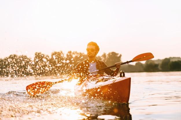 Genießen sie den tag auf dem kajak. hübscher junger mann, der auf see mit sonnenuntergang im hintergrund kajak fährt