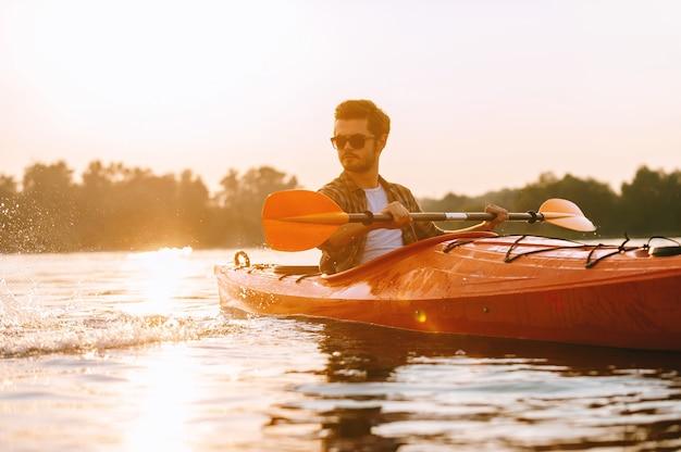 Genießen sie den tag auf dem wasser. hübscher junger mann, der auf see mit sonnenuntergang im hintergrund kajak fährt