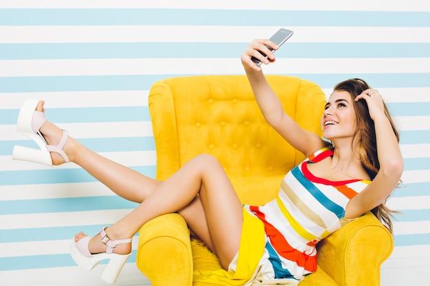 Genießen sie die sommerzeit der modischen hübschen jungen frau im bunten kleid, mit dem langen lockigen brünetten haar, das selfie im gelben stuhl auf gestreifter wand macht. spaß haben, urlaub, freizeit.
