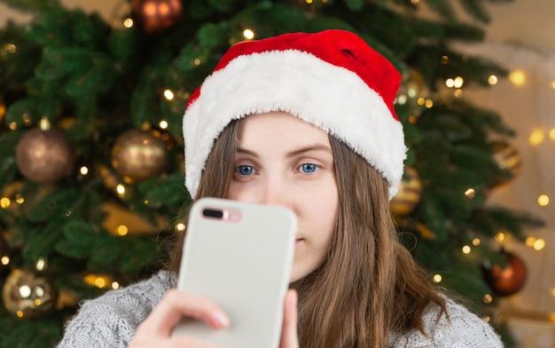 Genießen sie die weihnachtsatmosphäre. schließen sie herauf foto des positiven fröhlichen mädchens im weihnachtsmannhut