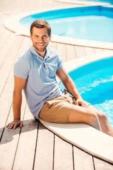 Genießen sie die zeit am pool. hübscher junger mann im poloshirt sitzt am pool und lächelt