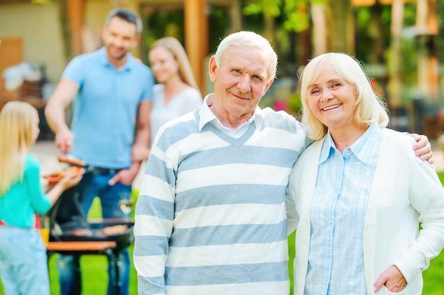 Genießen sie die zeit mit der familie. glückliches seniorenpaar, das sich miteinander verbindet und in die kamera schaut, während andere familienmitglieder im hintergrund essen grillen
