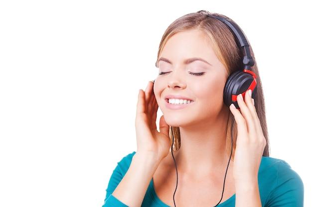 Genießen sie einen ausgezeichneten sound! fröhliche junge frauen, die hände an kopfhörern halten und lächeln, während sie vor weißem hintergrund stehen