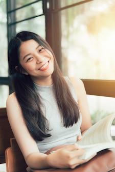 Genießen sie entspannende zeiten mit lesebuch, thailändisches jugendlich lächeln der asiatischen frauen mit buch im weinlesefarbton der kaffeestube