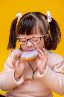 Genießen sie es schmecken. außergewöhnliches mädchen mit ungewöhnlichem gesicht kennzeichnet beißendes stück blauen donuts mit rosa elementen