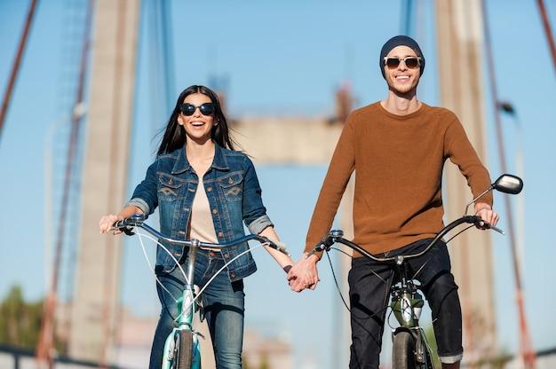 Genießen sie ihr aktives date. schönes junges paar, das fahrrad entlang der brücke fährt und lächelt