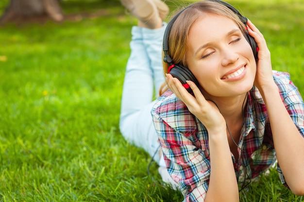 Genießen sie ihre lieblingsmusik in der natur. schöne junge frau mit kopfhörern, die musik hört und lächelt, während sie auf dem grünen gras liegt