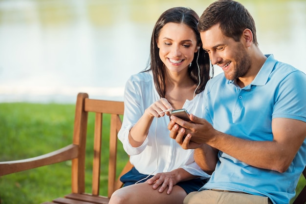 Genießen sie ihre lieblingsmusik zusammen. schönes junges liebespaar, das zusammen auf der bank sitzt, während die frau auf das handy zeigt und lächelt