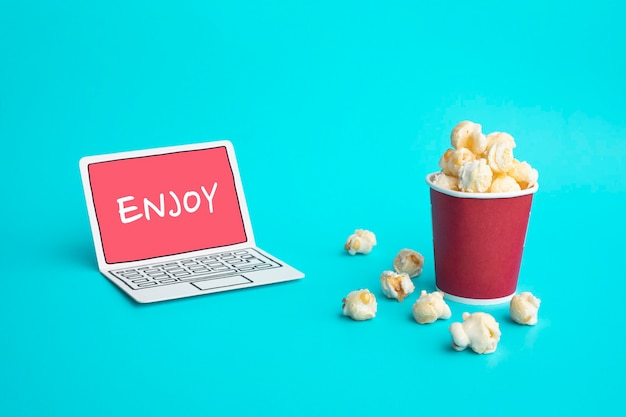 Genießen sie mit vdo unterhaltung oder filmkonzepten mit text auf papierkunst laptop und popcorn