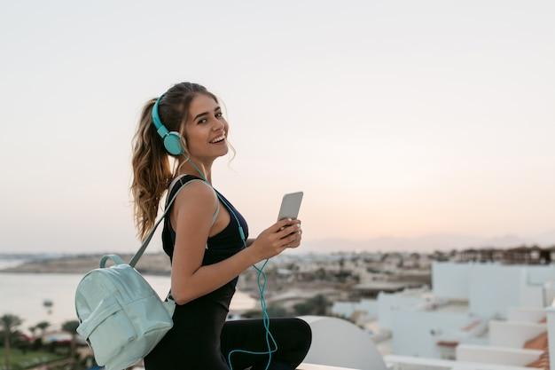 Genießen sie schöne musik über kopfhörer einer positiven, freudigen sportlerin, die bei sonnenaufgang am meer chillt. modisches modell, spaß haben, lächeln.