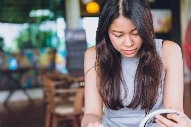 Genießen sie, sich zeiten mit lesebuch, thailändischem jugendlich ernstem fokus der asiatinnen zu entspannen, um taschenbuch im weinlesefarbton der kaffeestube morgens zu lesen