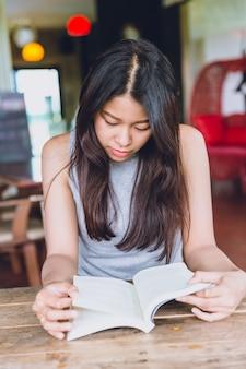 Genießen sie, sich zeiten mit lesebuch, thailändischem jugendlich ernstem fokus der asiatinnen zu entspannen, um taschenbuch in der kaffeestube zu lesen