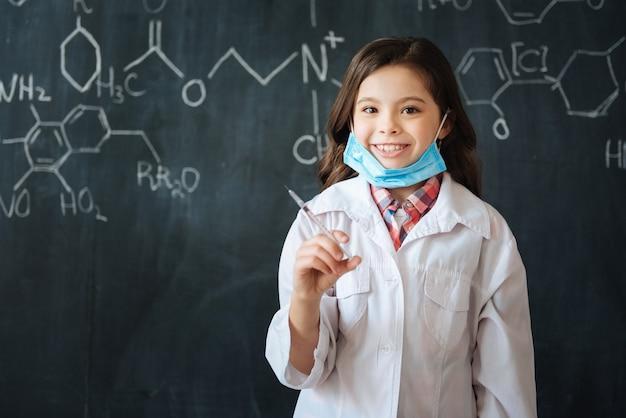 Genießen sie unterricht für zukünftige mediziner. charmantes geschicktes fröhliches mädchen, das nahe der tafel im labor steht, während medizinunterricht genießt und die spritze hält