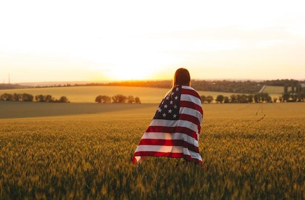 Genießende frau mit amerikanischer flagge in einem weizenfeld bei sonnenuntergang. 4. juli. unabhängigkeitstag, patriotischer feiertag.