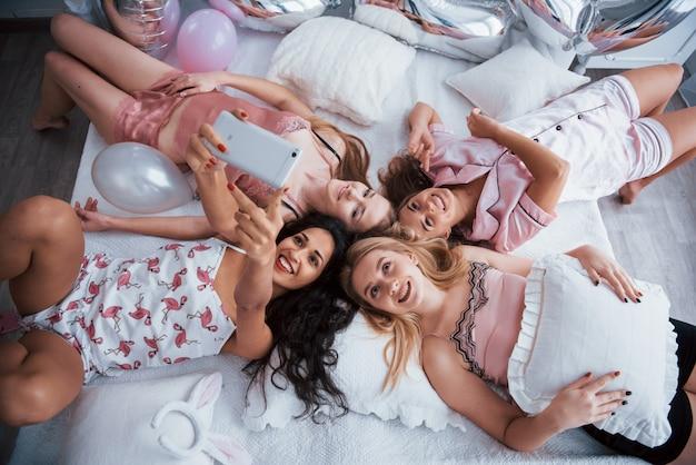 Genießt es, sich zu treffen. selfie mit freunden nehmen, während auf dem bett auf junggesellenabschied liegen