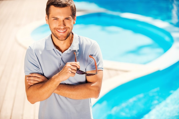 Genießt seinen sommerurlaub. draufsicht auf einen fröhlichen jungen mann im poloshirt, der am pool steht und ihnen lächelt
