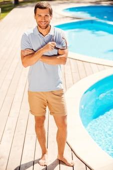 Genießt seinen sommerurlaub. voller länge eines gutaussehenden jungen mannes im poloshirt, der am pool steht und dich anlächelt