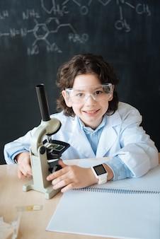 Genommutationen erforschen. glückliches fähiges brillantes kind, das im labor sitzt und wissenschaftsunterricht genießt, während notizen macht und mikroskop benutzt