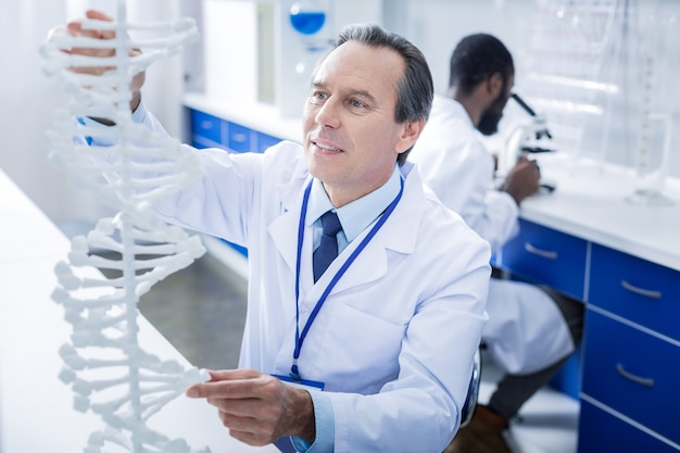 Genomstudien. netter ernsthafter männlicher wissenschaftler, der das dna-modell betrachtet und es während einer recherche berührt